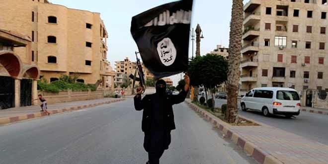 أحد أعضاء التابعين لداعش يرفع علمها في مدينة الرقة - رويترز